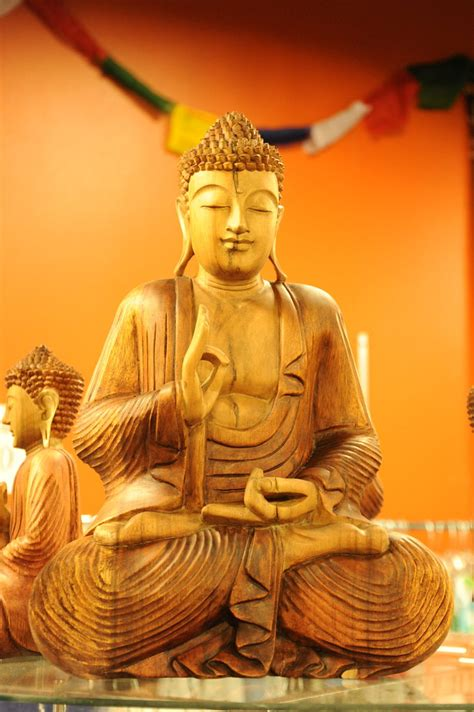 Carved Buddha statue in wood, slight smile, eyes closed, d